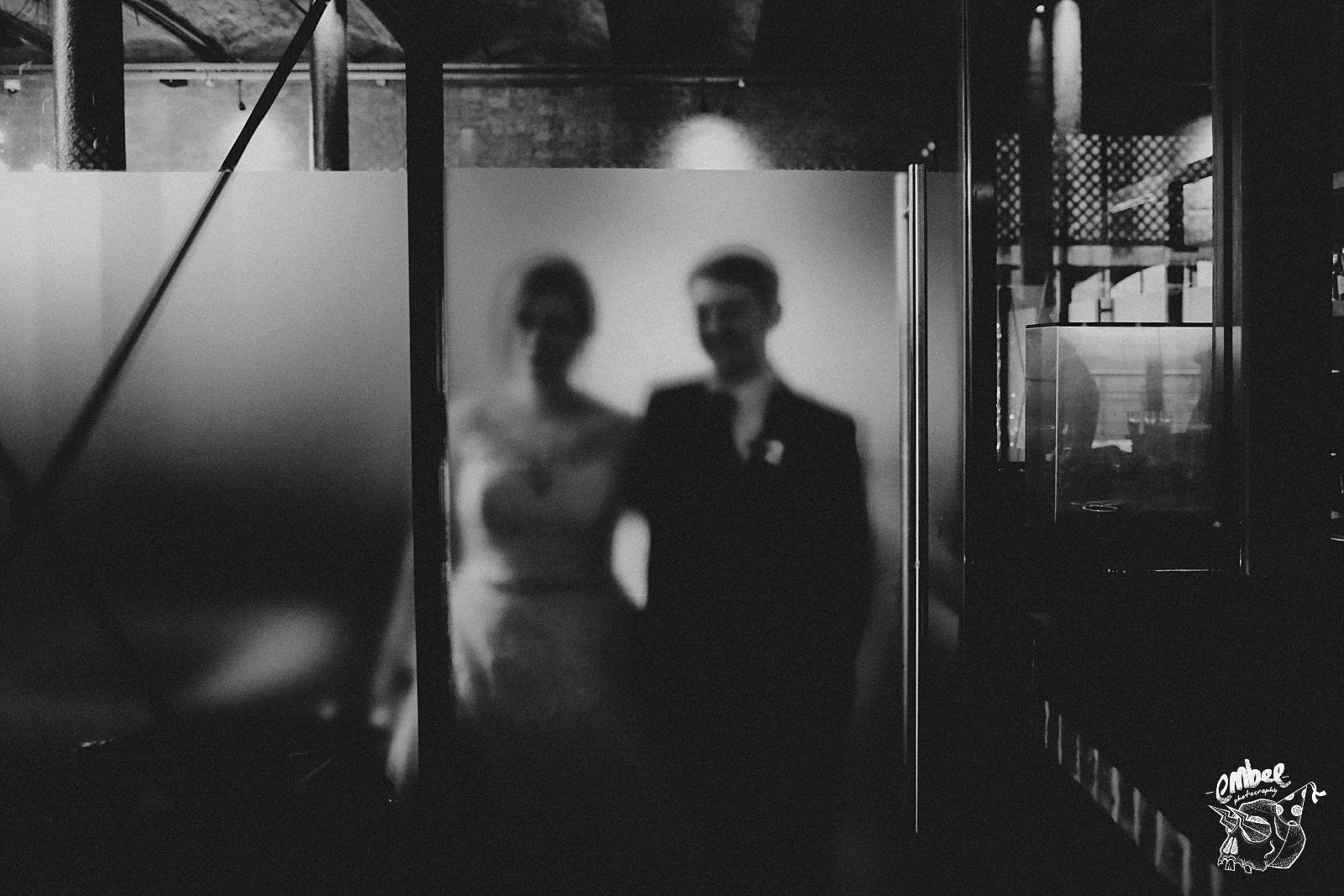 bride and groom behing frosted glass