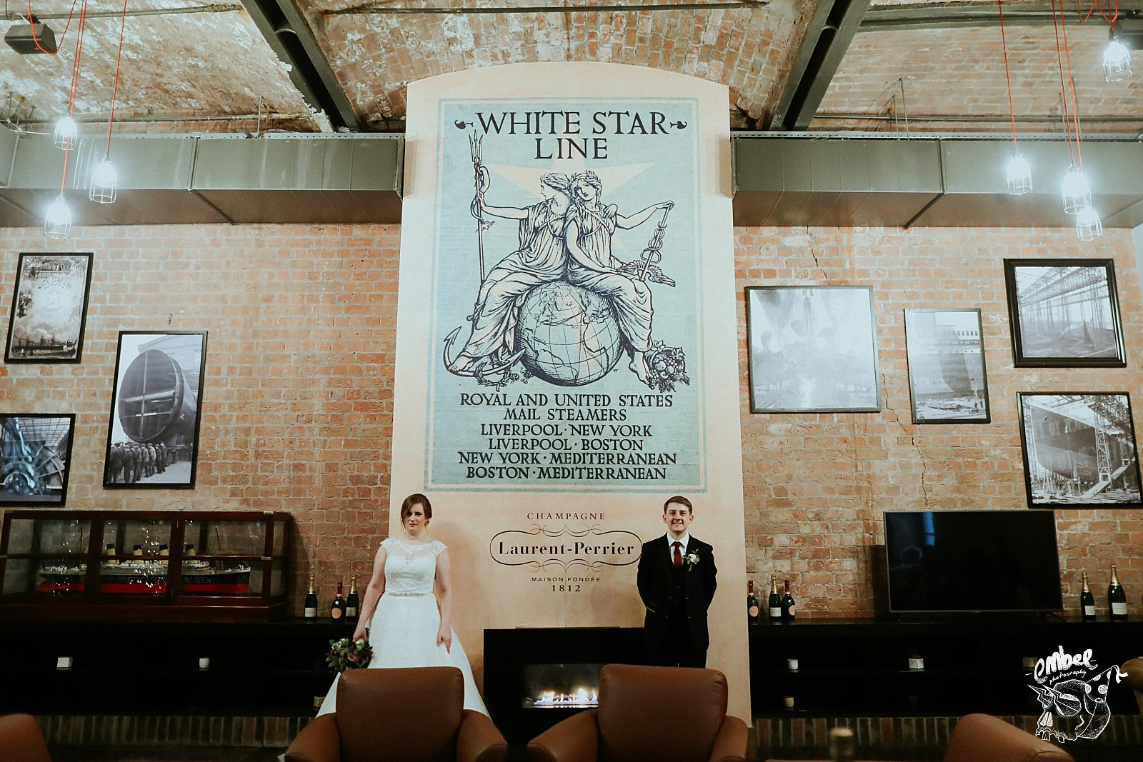 bride and groom in front of a white star line mural