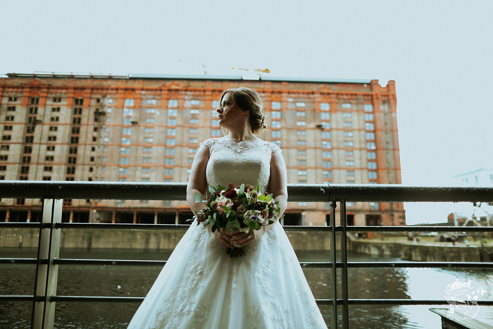 brides portrait with big industrial warehouse behing her