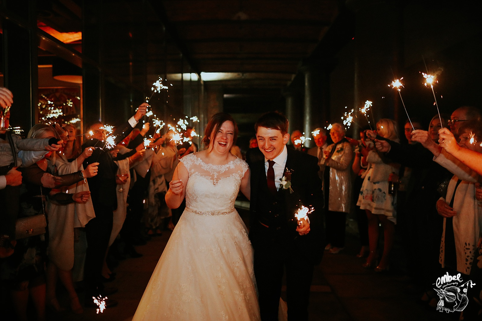 bride and groom walking with sparklers