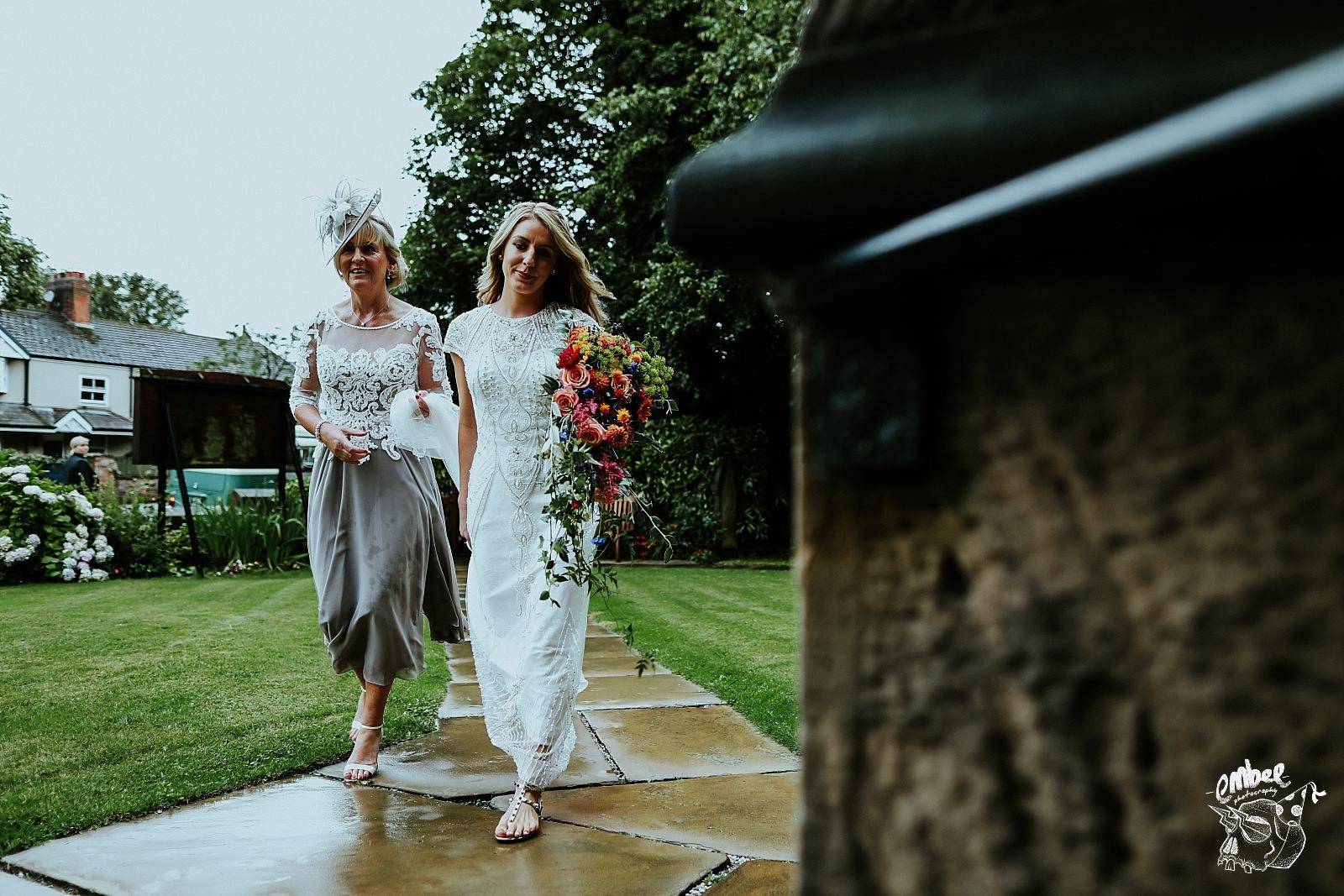 brides walks with mum down church path