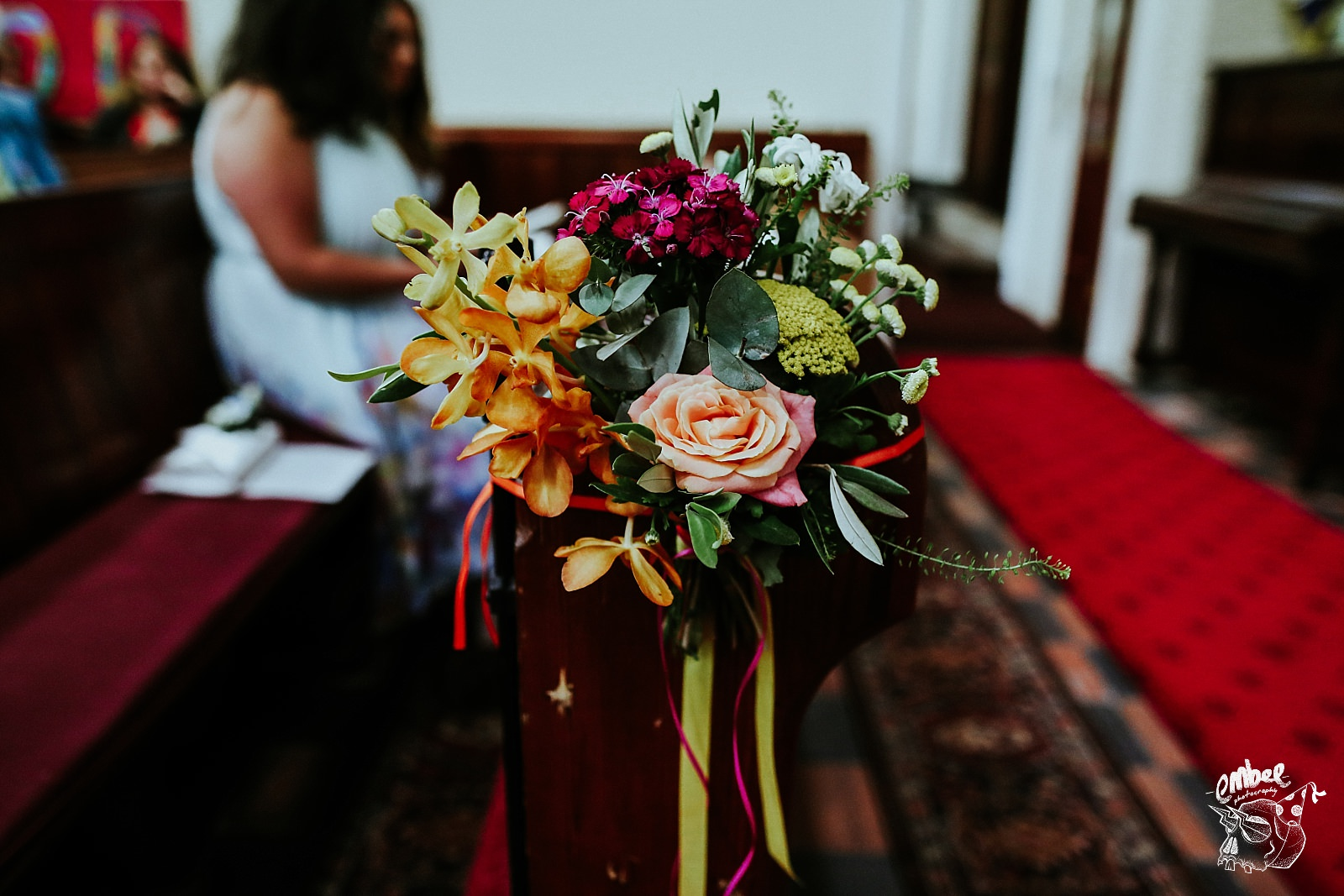 wedding flowers on end of pew in church