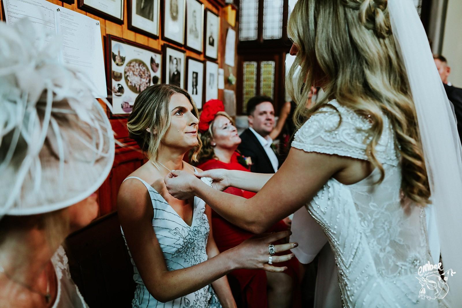 bride fixes bridesmaids necklace