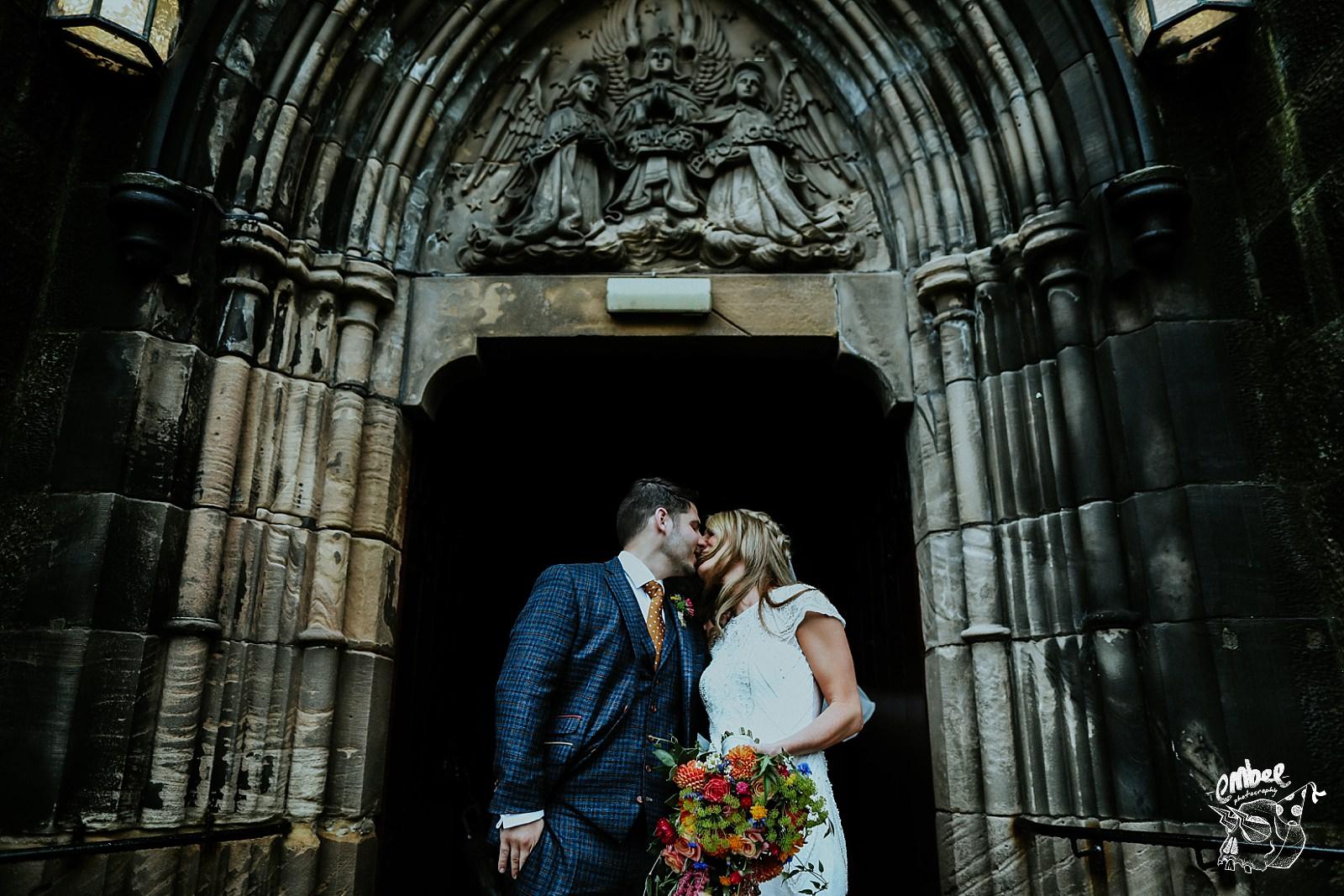 bride and groom kissing in church doorway