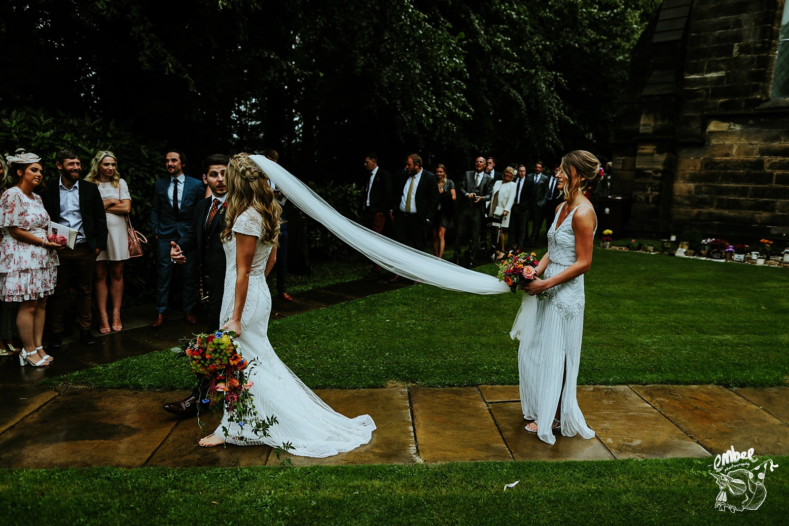 bridesmaid holding brides veil walking out of church