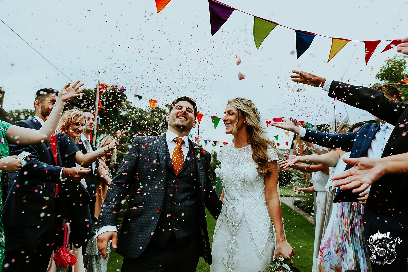 bride and groom walking throgh confetti