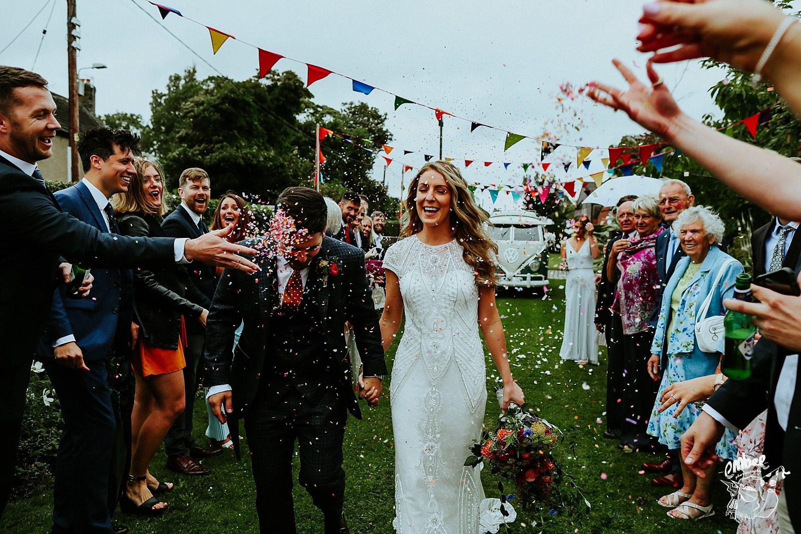 bride and groom walking throgh confetti