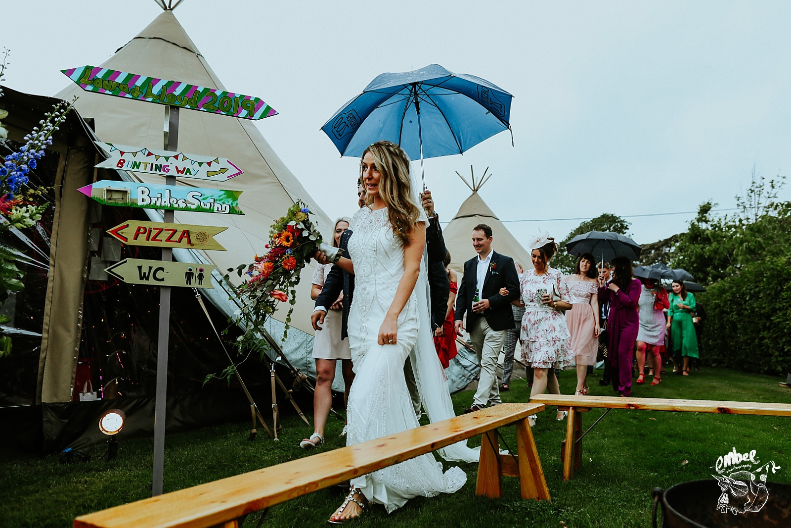bride walking with guests in the rain