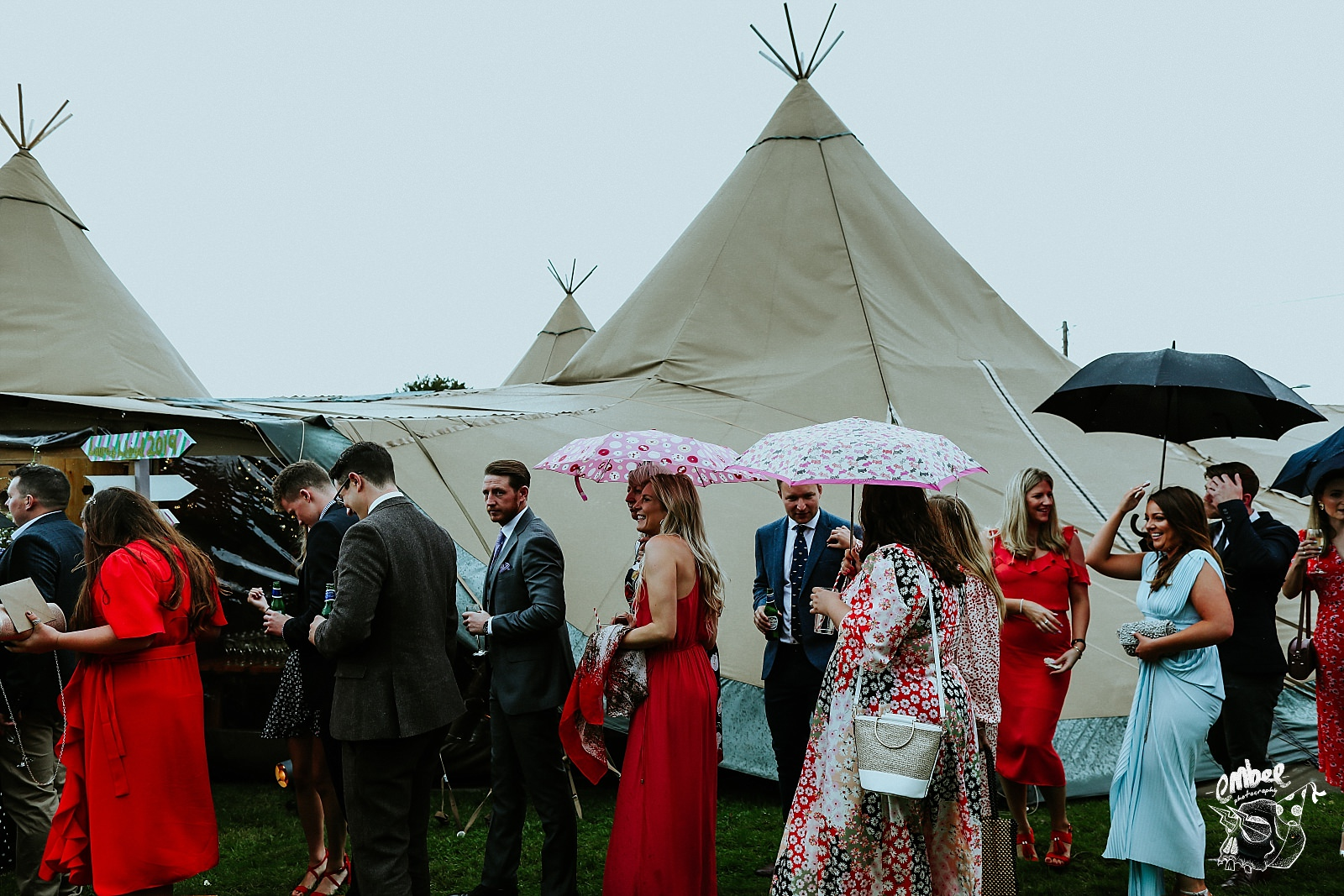 guests walking in the rain with umbrellas