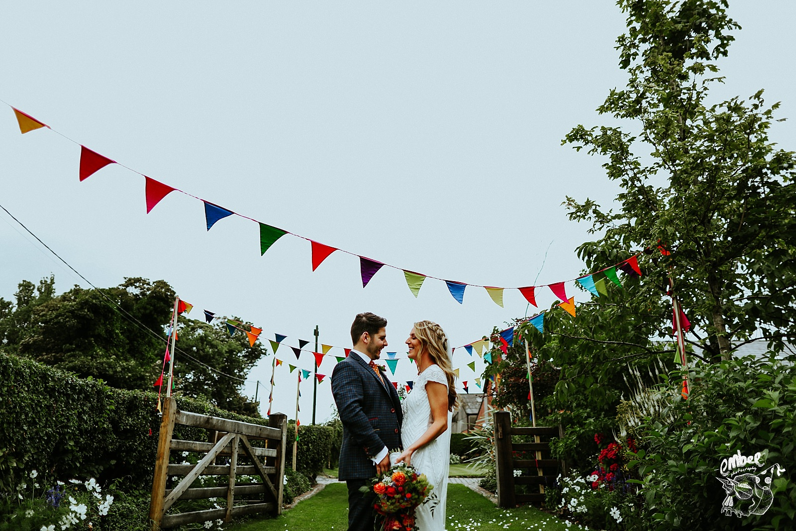 bride and groom under bunting holding each other