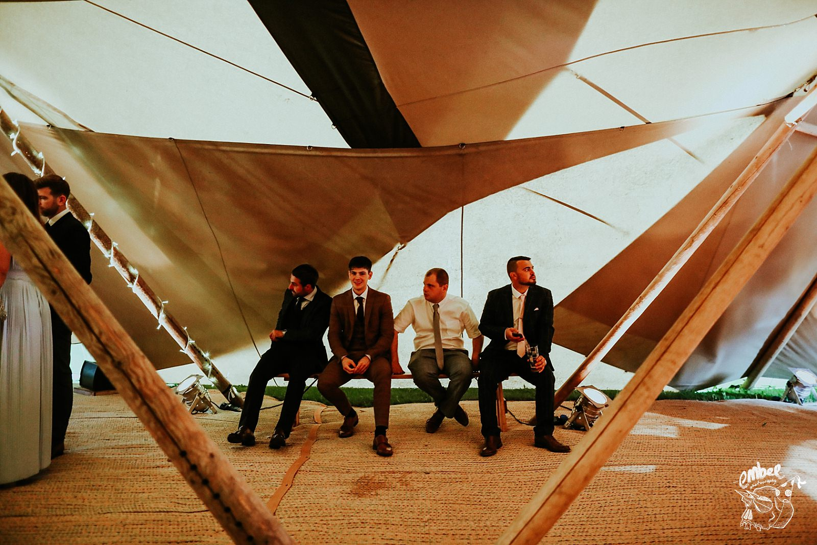 four men on a bench in teepee