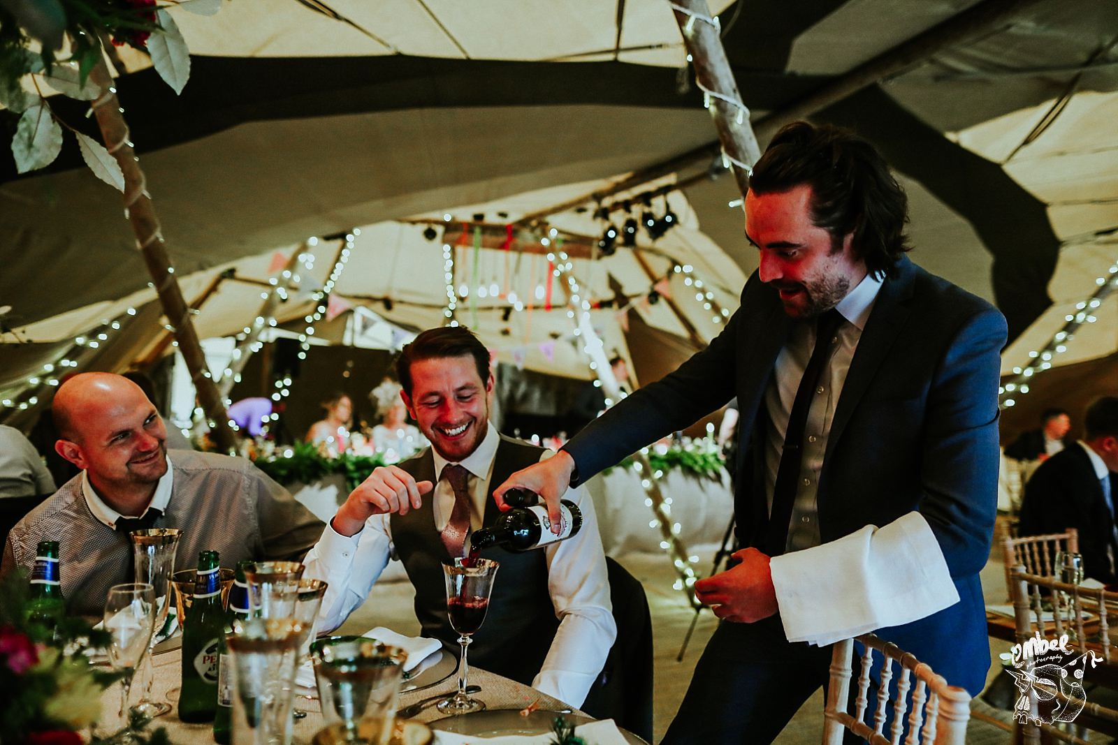 guest acting funny pouring peoples drinks at wedding