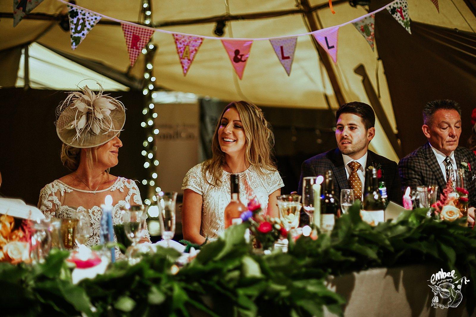 bride laughing inside of wedding tipi