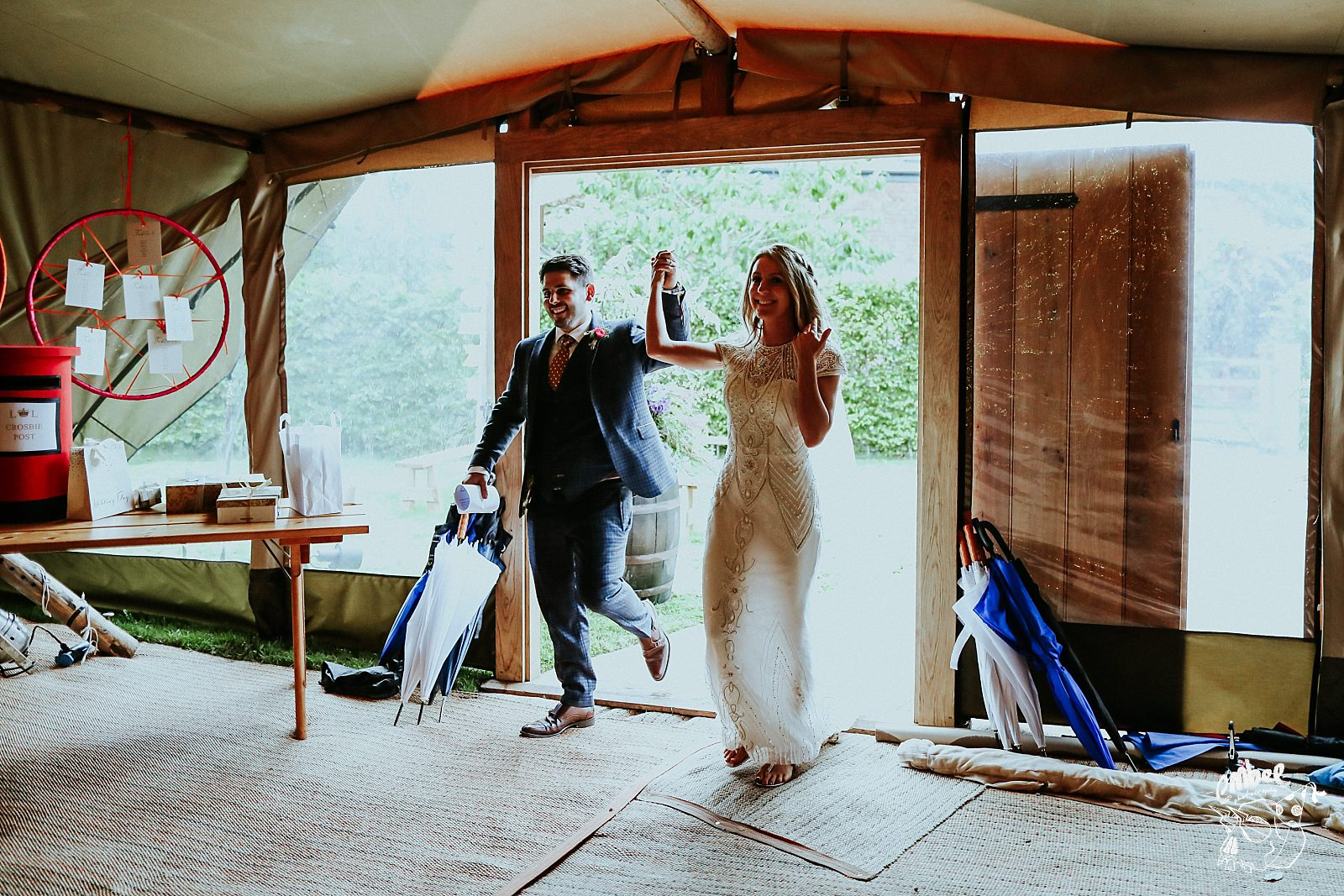bride and groom walk into tipi to all guests