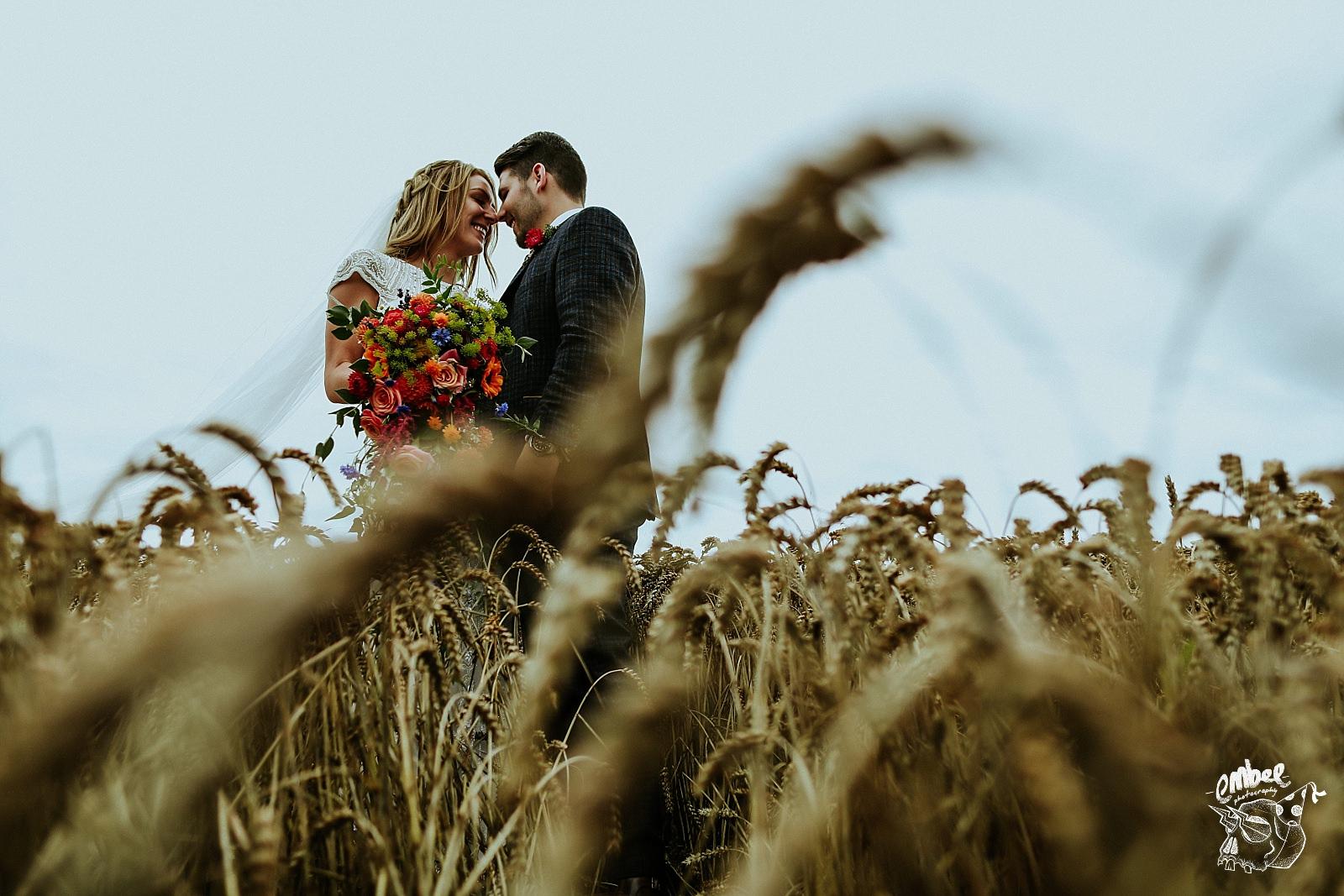 couple getting cute in wheat field
