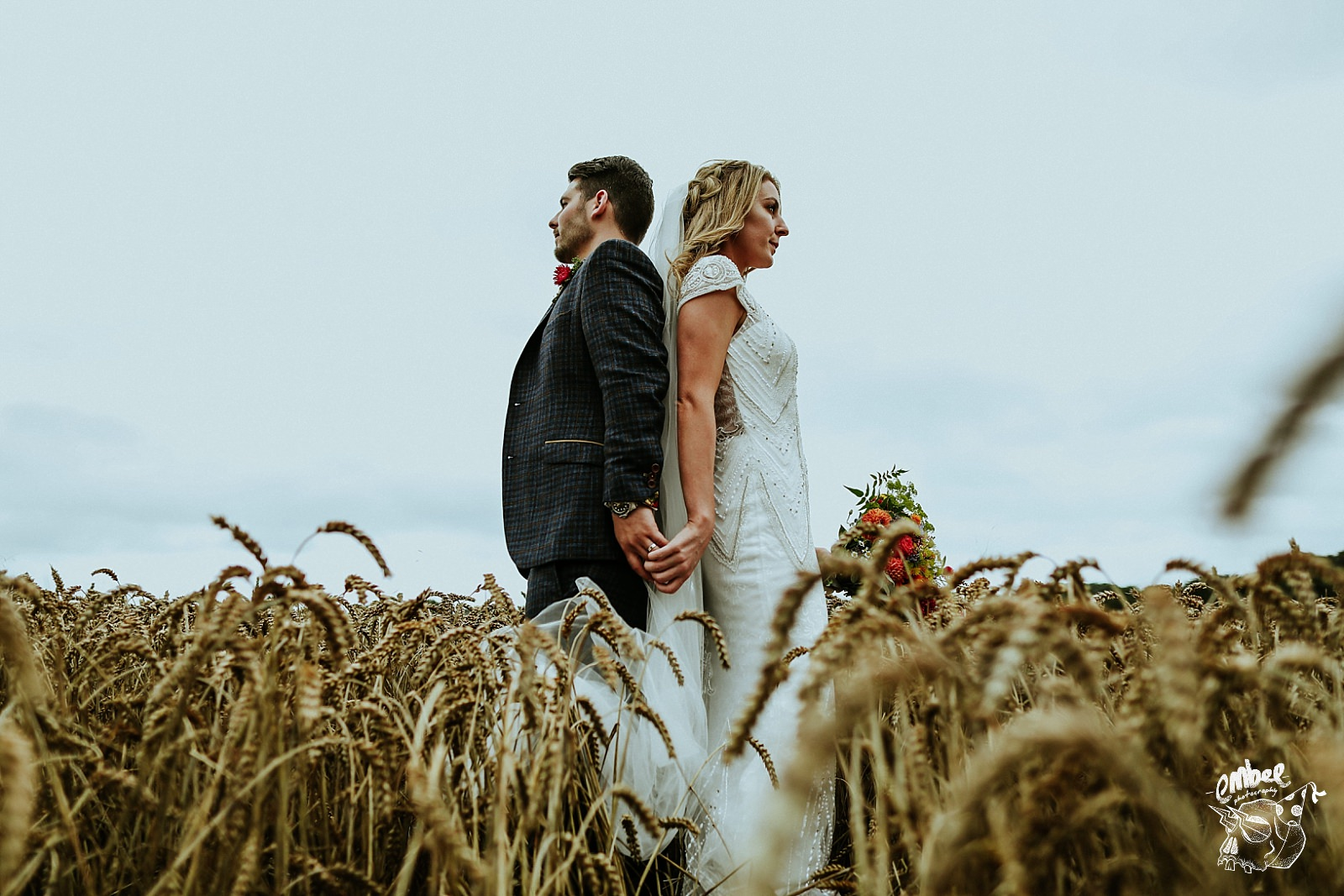 bride and groom standing back to back in wheatfield