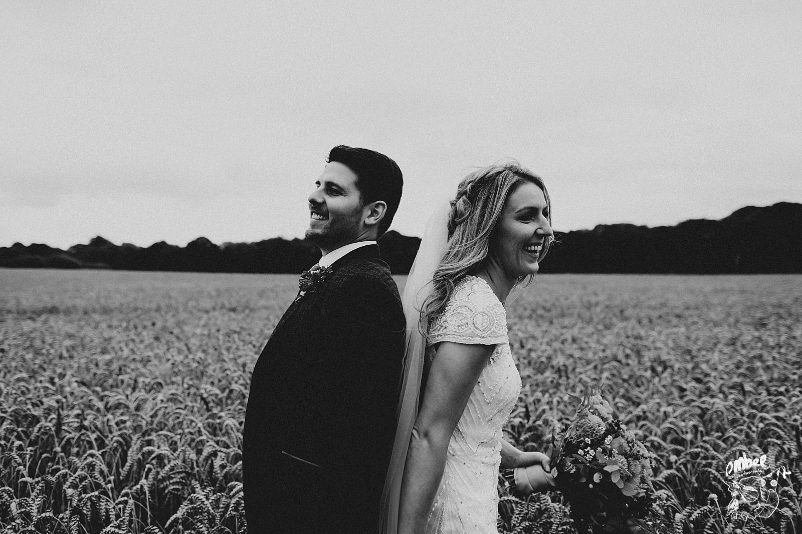 back to back bride and groom in field