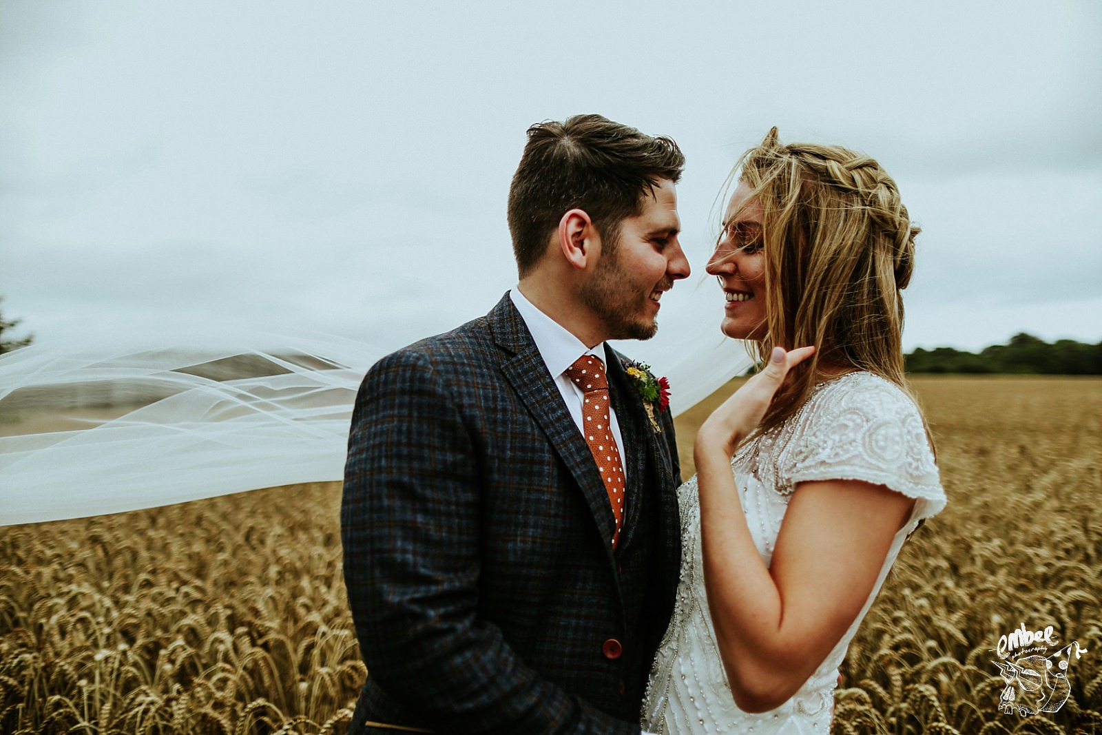 bride and groom getting close in a cornfield