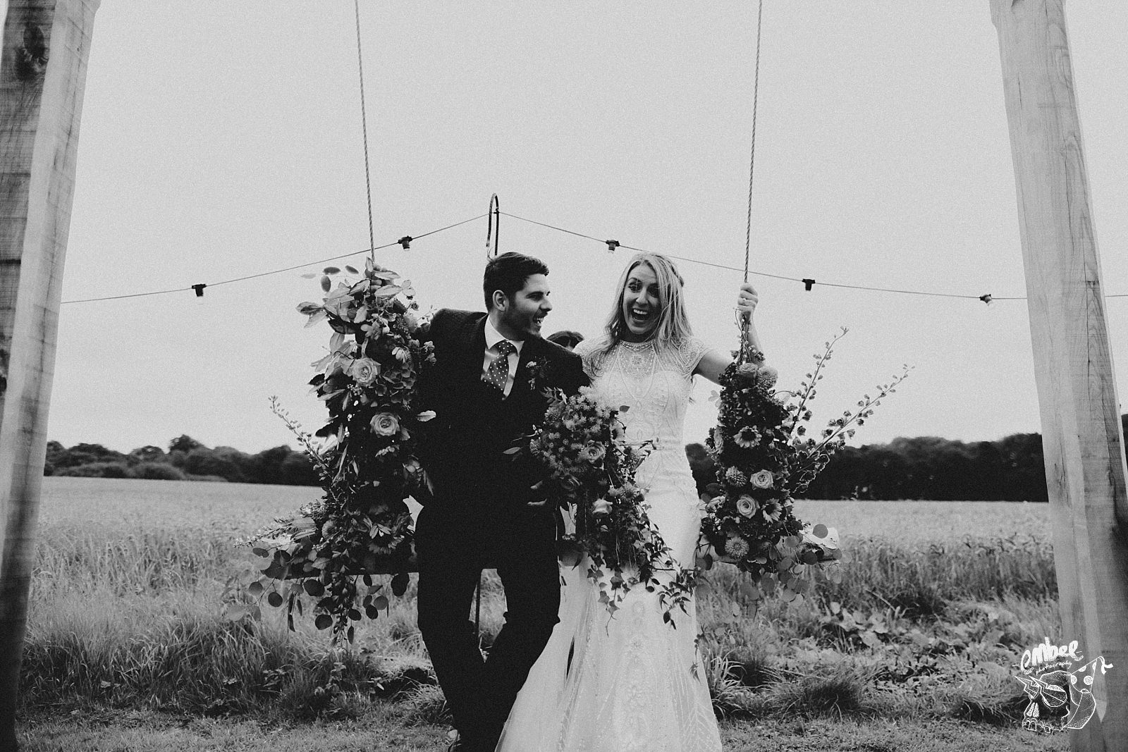 bride and groom laughing on a swing