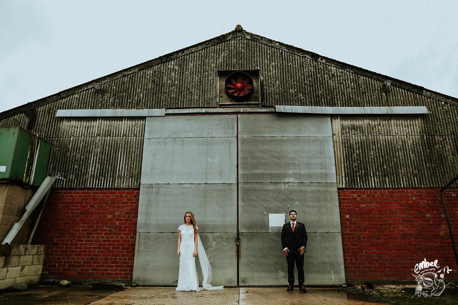 bride and groom stand infront of steel doors of a barn