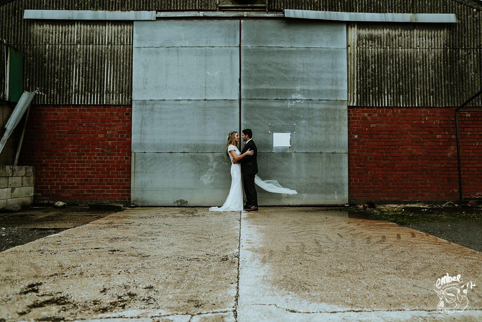 brdie and groom infront of steel doors