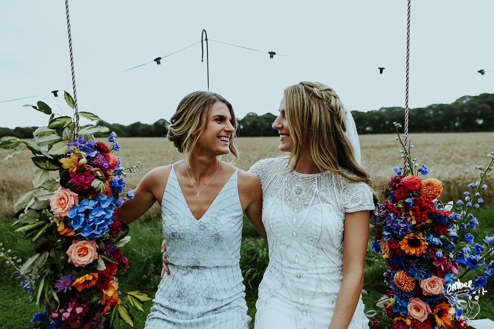 bride and sister on swing with flowers
