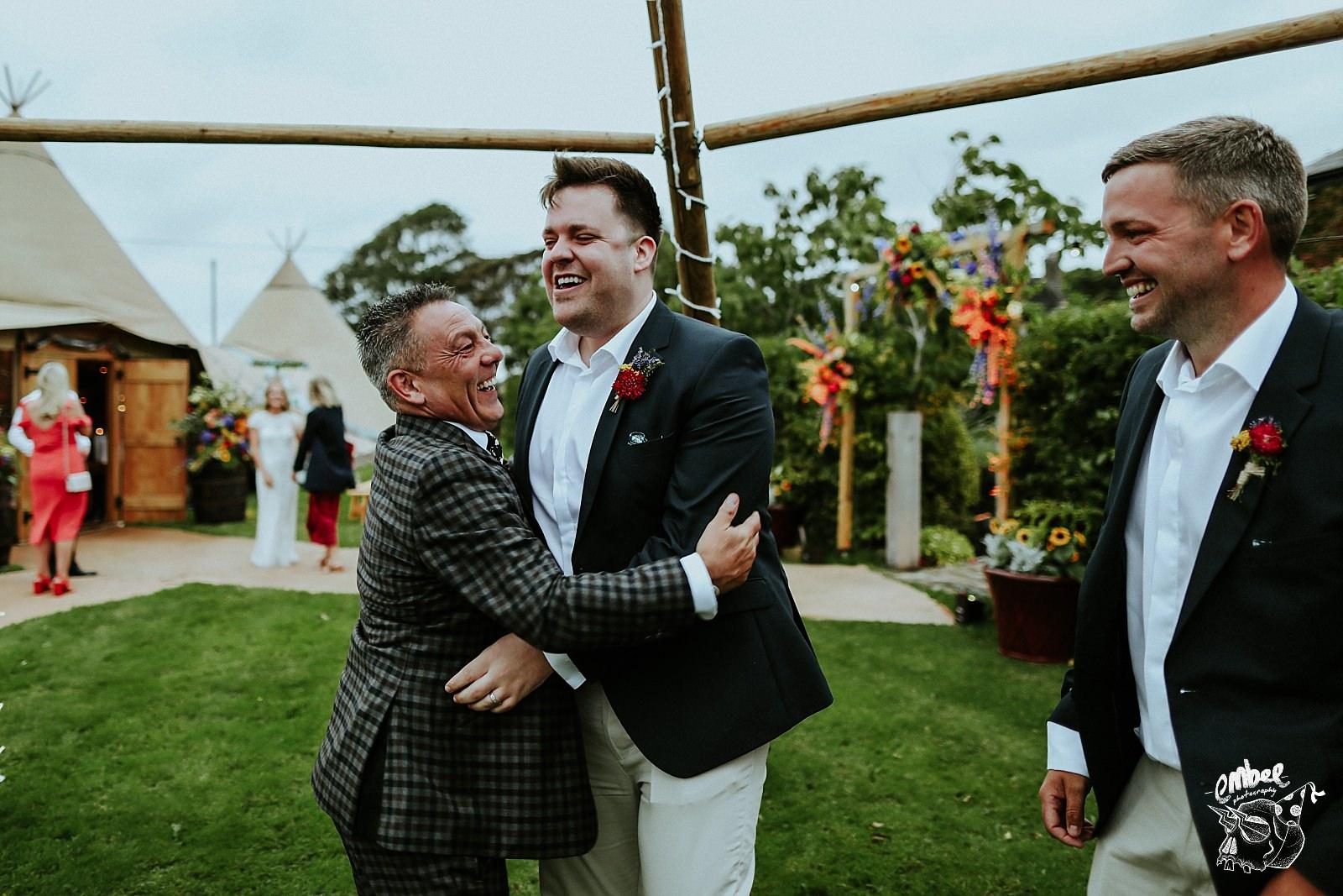 grooms dad hugging groomsman
