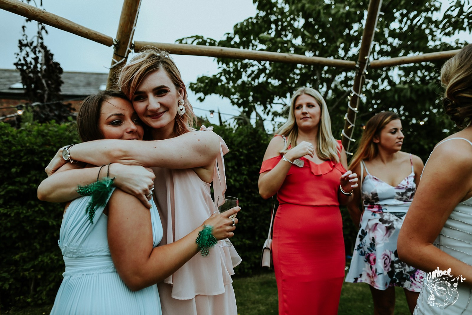 two friends hug at their friends wedding