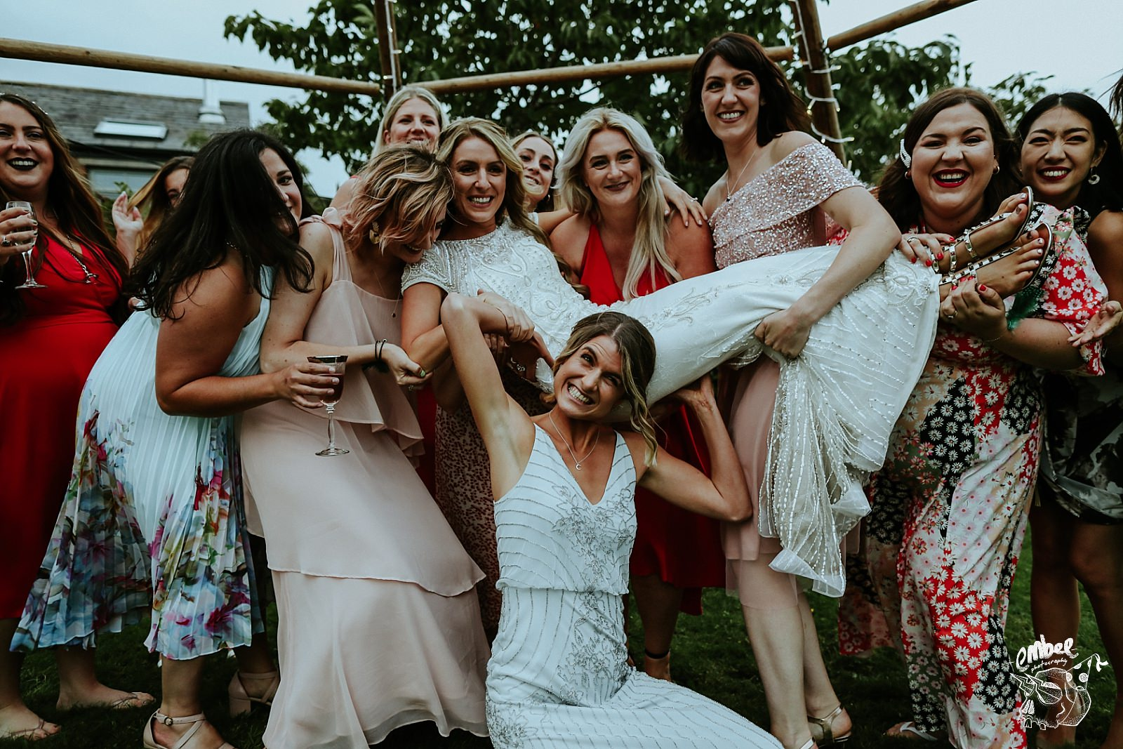 bridemaids lift up bride on her wedding