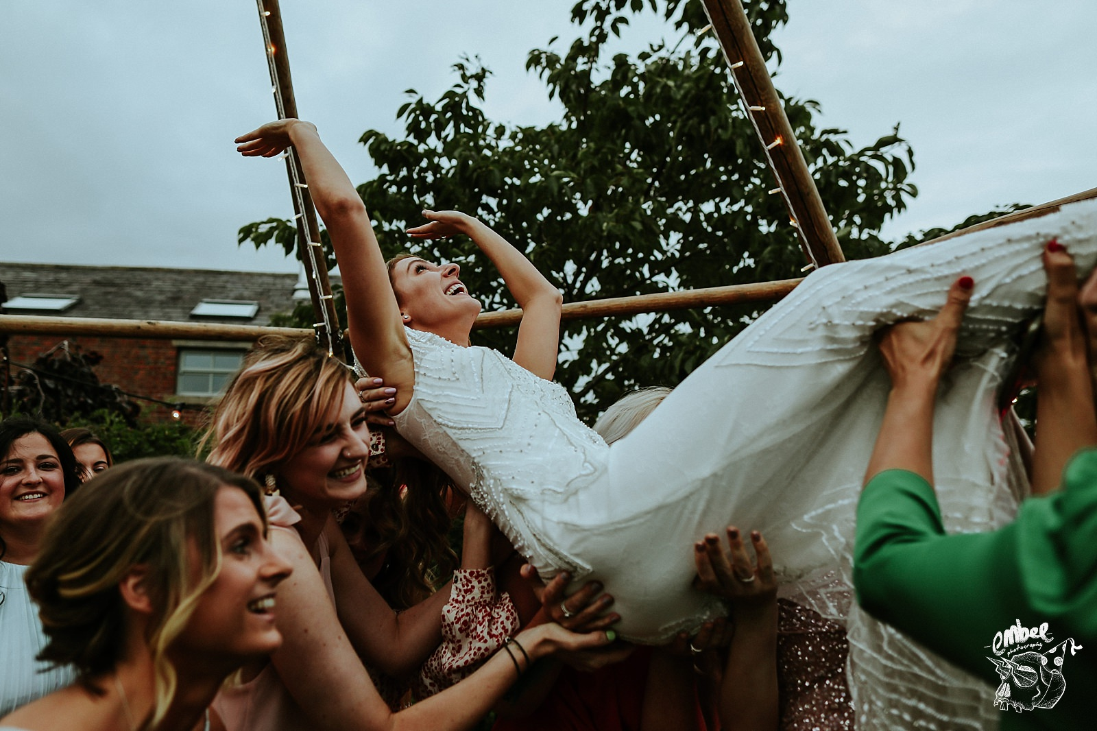 friends lift bride up under a tipi