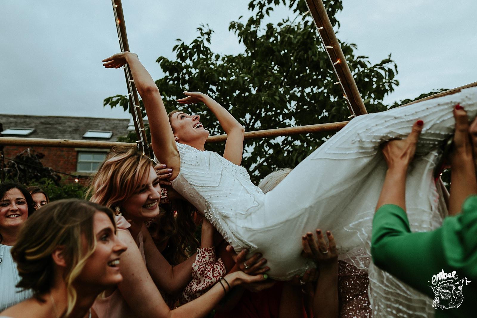 friends lift bride up under a tipi