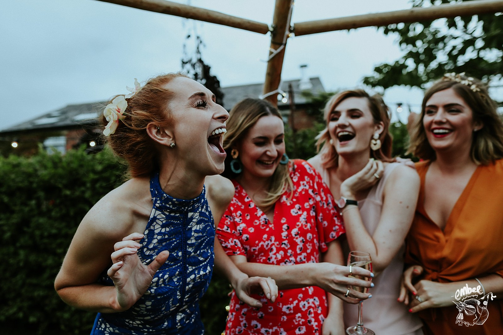 woman laughing with mates at wedding