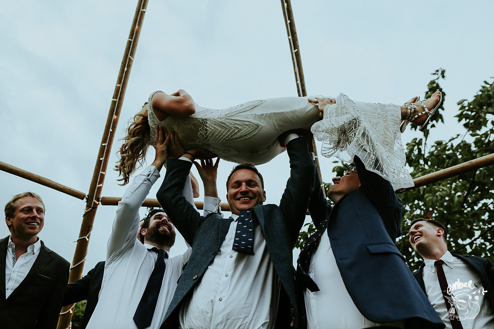 groomsman lifts the bride above his head