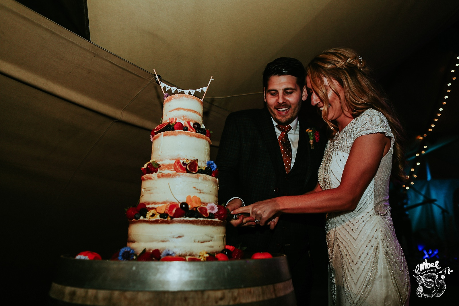 bride and groom cut cake at their wedding