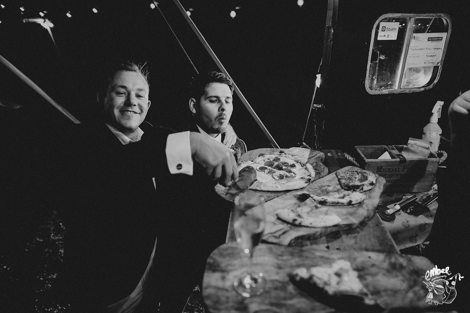 men with pizza at wedding