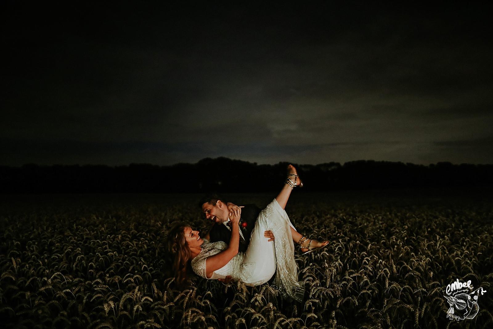 groom picks up bride in wheatfield