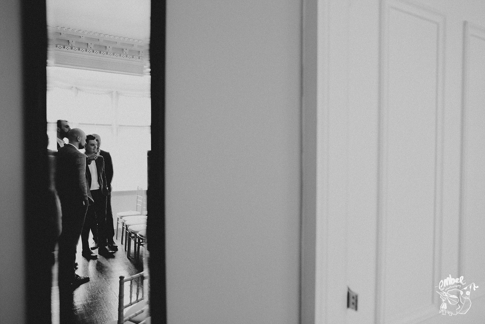looking at the groomsman through an open door