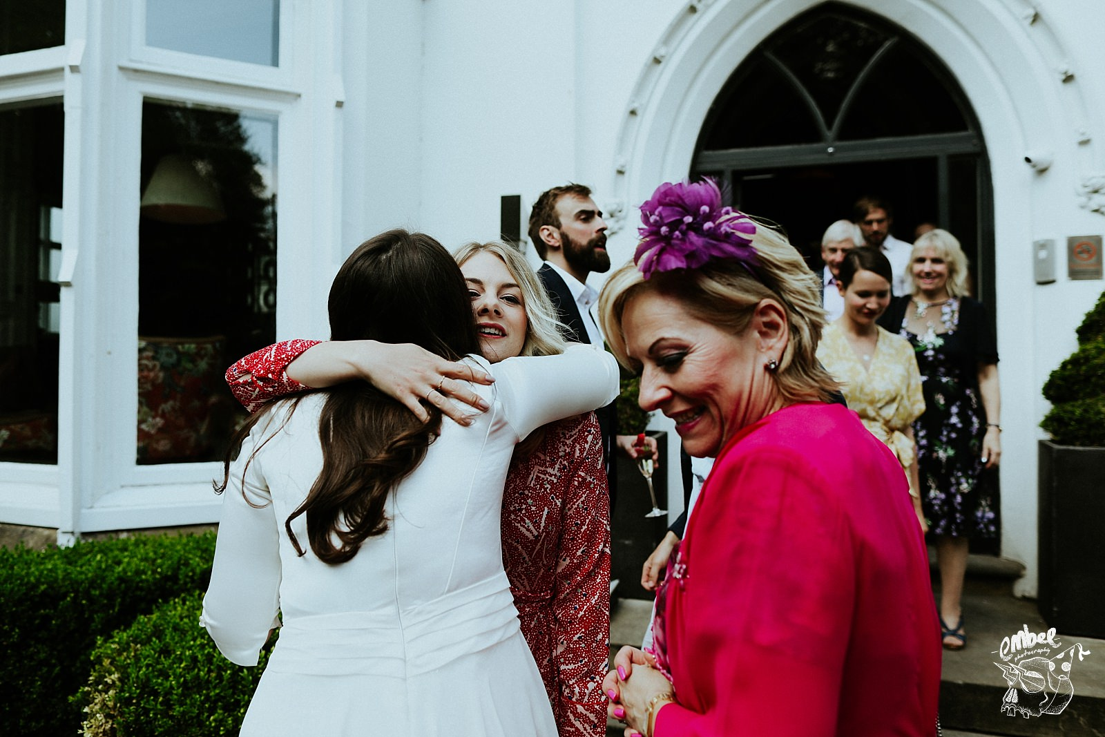 bride gets hugs at wedding