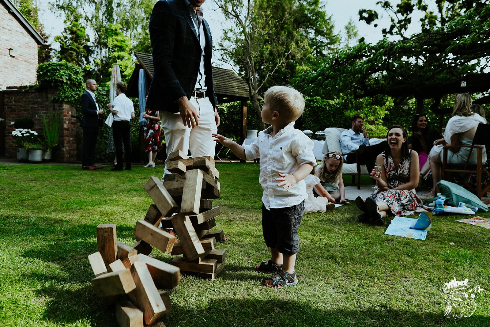 kids knocks down jenga tower at wedding