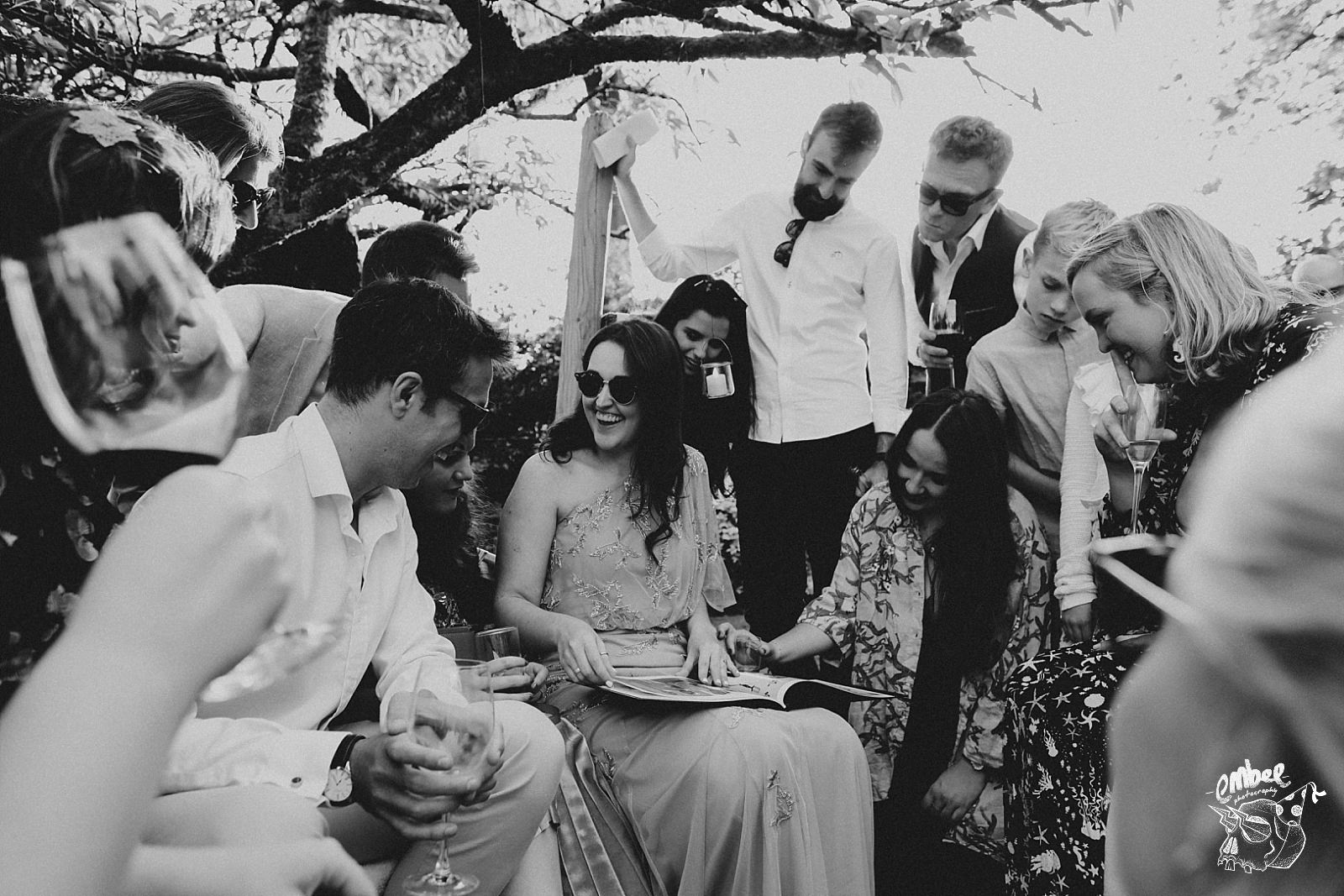 everyone gathered around the bride looking at groom baby pictures