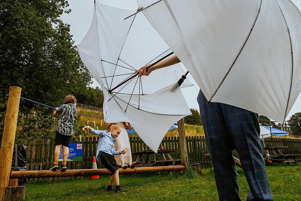 kids playing with umbrellas at wedding