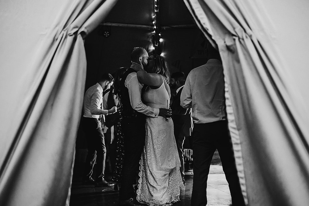 bride and groom kiss in a tipi