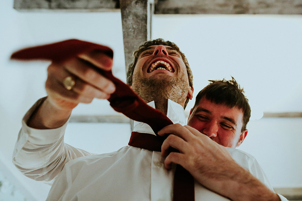best man tying the groom tie and laughing